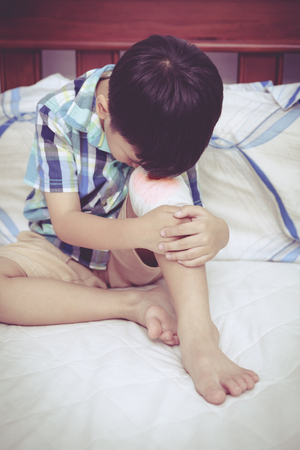 injurious: Child injured on bed in bedroom. Bloody wound on the childs knee with bandage. Sad boy. Human health care and medicine concept. Vintage style. Stock Photo