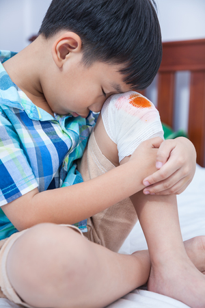 boy bedroom: Child injured on bed in bedroom. Bloody wound on the childs knee with bandage. Sad boy. Human health care and medicine concept. Stock Photo
