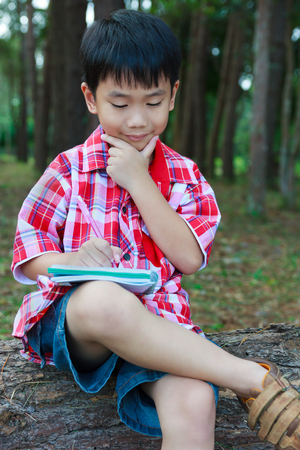 resolve: Handsome asian boy can resolve problem, happy and smiling on wooden log in national park. Child writing on notebook. Outdoors in the day time with sunlight. Children planning and education concept.