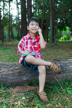 Handsome asian boy thinking to solve a problem on wooden log in national park. Outdoors in the day time with bright sunlight. Children planning and education concept. Stock Photo