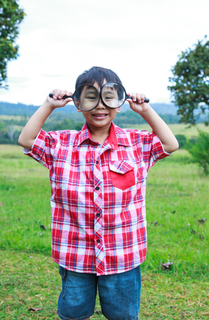 peers: Playful asian child enjoying at park. Young handsome boy peers at the camera through two magnifying glass on blurred nature background. Outdoors in the day time with bright sunlight. Stock Photo