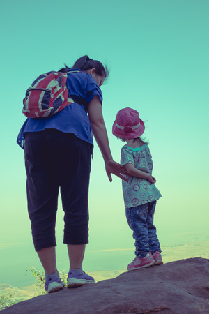 cross process: Back view of mother and child hikers enjoying the view at the top of a mountain at the day time. Friendly family. Cross process. Stock Photo