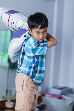 An aggressive asian child. Boy looking furious. Kid will throw pillow inside bedroom. Negative human face expressions, emotions, reaction, conflict, confrontation, problem families concept.