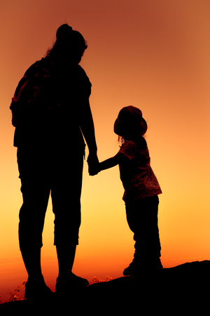 clasping: Silhouette back view of mother and daughter clasping hand together at sunset on vacation. Colorful sky background orange and gold colors sunset sky. Friendly family.