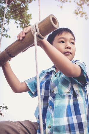 rope ladder: Handsome asian boy climbing on rope ladder made of wood. Child playing outdoors. Travel and adventure concept. Vintage style. Stock Photo