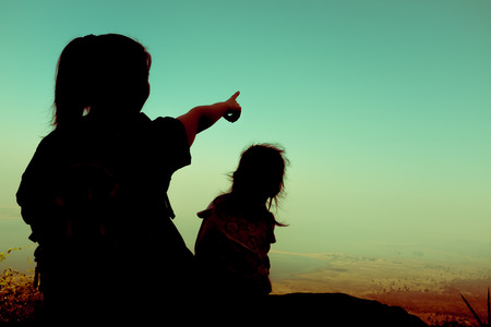 cross process: Back view of young mother and child hikers enjoying the view at the top of a mountain at the day time. Woman pointing to empty copy space at sky. Friendly family. Cross process.