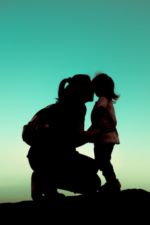 parentage: Silhouette side view of a young mother lovingly kissing her little child in front of a sunset in the sky on a summer day. Friendly family. Cross process.