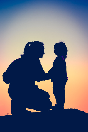 cross process: Silhouette side view of young mother and child hikers enjoying the view at the top of a mountain. Colorful sunset sky background. Friendly family. Cross process. Vintage picture style.
