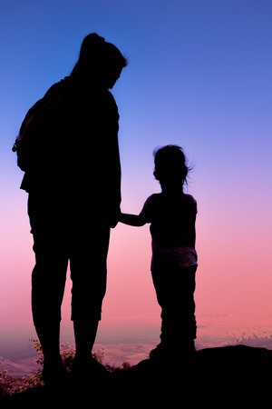 parentage: Silhouette back view of mother and child hikers enjoying the view at the top of a mountain. Colorful sunset sky background. Friendly family.