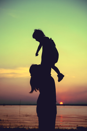 parentage: Silhouette of mother and child enjoying the view at riverside. Mother lifting her little girl up in the air on colorful sunset sky background. Friendly family. Cross process. Vintage style.