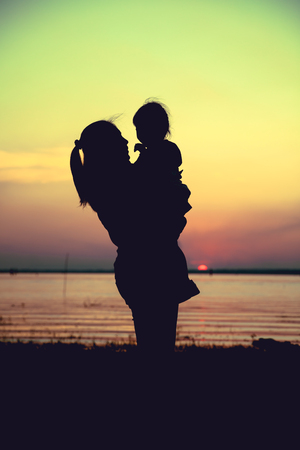 carrying the cross: Silhouette of mother and child enjoying the view at riverside. Mother carrying her daughter on colorful sunset sky background. Friendly family. Cross process. Vintage style.