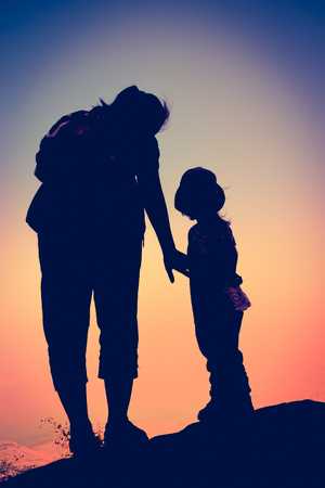cross process: Silhouette back view of mother and child hikers enjoying the view at the top of a mountain. Colorful sunset sky background. Friendly family. Cross process. Vintage style.