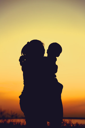 parentage: Silhouette of mother and child enjoying the view at riverside. Mother hugging her son on colorful sunset sky background. Friendly family.