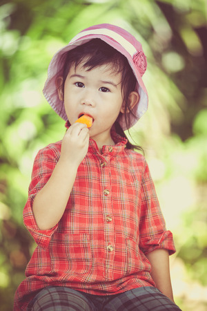 cross process: Little asian girl wearing pink hat and eating ice cream in the summer on blurred nature background. Pretty child in nature. Outdoors. Cross process. Stock Photo