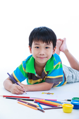 strengthen: Handsome asian boy lie on the floor looking at camera and smiling. Concepts of creativity and education, strengthen the imagination of child. Studio shot. On white background.
