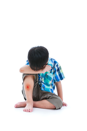 injurious: Little sad boy bare feet sitting on floor, bruise on leg after accident, child painful. Isolated on white background. Negative human emotions. Free form copy space.
