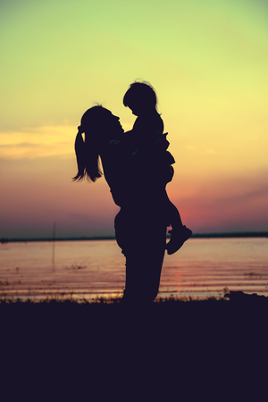 cross process: Silhouette of mother and child enjoying the view at riverside. Mother carrying her daughter on colorful sunset sky background. Friendly family. Cross process. Vintage style.