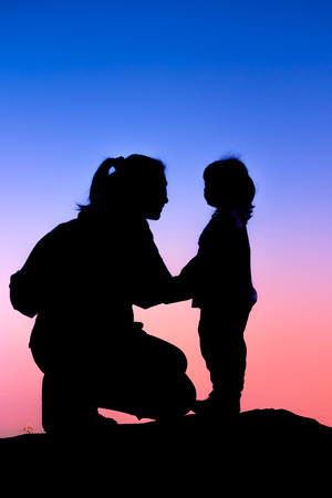 parentage: Silhouette side view of young mother and child hikers enjoying the view at the top of a mountain. Colorful sunset sky background. Friendly family.