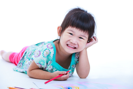 strengthen: Pretty asian girl lie on the floor looking at camera and smiling. Concepts of creativity and education, strengthen the imagination of child. Studio shot. On white background.