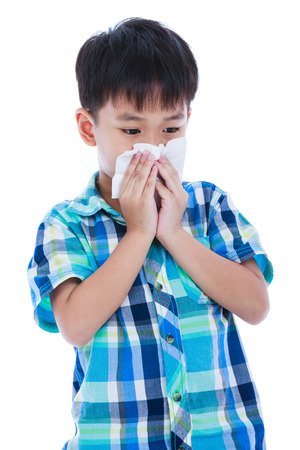 Childhood, healthcare and medicine concept. Handsome asian boy blowing his nose into tissue. Sick child with allergy symptom. Isolated on white background. Studio shot.