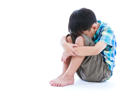 ni�os abandonados: Little sad boy barefeet sitting on floor. Isolated on white background. Negative human emotions. Conceptual about children who lack warmth and affection, abandoned children. Free form copy space. Foto de archivo