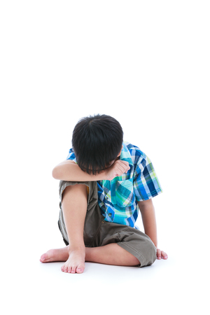 Little sad boy bare feet sitting on floor. Isolated on white background. Negative human emotions. Conceptual about children who lack warmth and affection, abandoned children. Free form copy space. Stock Photo