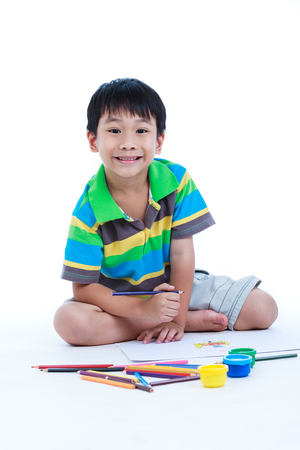 strengthen: Handsome asian boy sitting on the floor, looking at camera and smiling. Concepts of creativity and education, strengthen the imagination of child. Studio shoot. On white background.