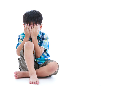 unloved: Full body. Little sad boy covered his face with hands. Isolated on white background. Negative human emotions. Conceptual about children who lack warmth and affection. Free form copy space. Stock Photo