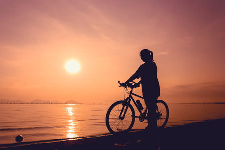 seaside: Silhouette of healthy biker-girl enjoying the view at seaside, on colorful sunset orange sky background. Reflection of sun in water. Active outdoor lifestyle concept. Outdoors. Stock Photo