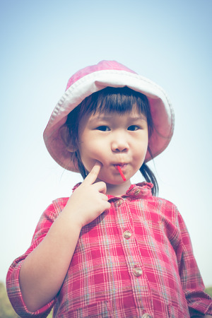 cross process: Cute little asian girl eating a lollipop on nature background in summertime. Child wearing pink hat and looking at camera. Cross process. Vintage style. Stock Photo