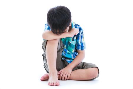 niños abandonados: Niño pequeño pies desnudos triste sentado en el suelo. Aislado en el fondo blanco. emociones humanas negativas. Conceptual acerca de los niños que carecen de calidez y afecto, los niños abandonados. Foto de archivo