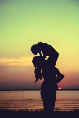 cross process: Silhouette of mother and child enjoying the view at riverside. Mother lifting her little girl up in the air on colorful sunset sky background. Friendly family. Cross process. Vintage style.