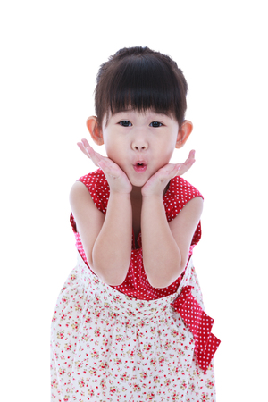 mouth opened: Wow. Adorable asian girl in beautiful dress looking excited holding her mouth opened, hands on cheek. Shocked surprised stunned. Positive human emotion. Studio shot. Isolated on white background Stock Photo