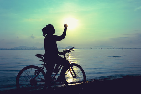 mountainbike: Silhouette of happy female with mountain-bike on colorful blue sky background. Active outdoors lifestyle for healthy concept. Action of winner or successful people.