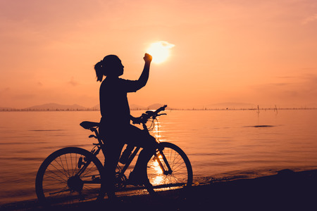 mountainbike: Silhouette of happy female with mountain-bike on colorful orange sky background. Active outdoors lifestyle for healthy concept. Action of winner or successful people. Stock Photo