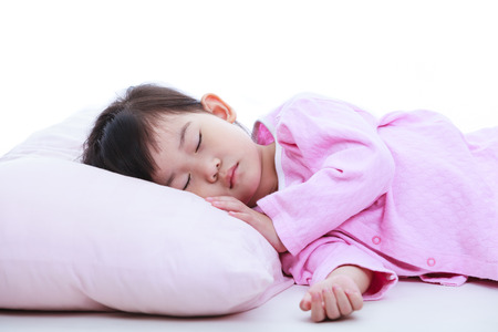 peaceful: Healthy children concept. Close up of little asian child sleeping peacefully. Adorable girl in pink pajamas taking a nap.