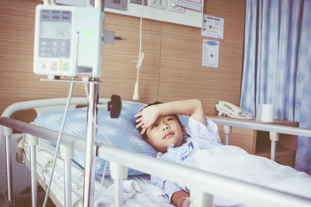sickbed: Illness Asian boy lying on sickbed in hospital with infusion pump intravenous IV drip.