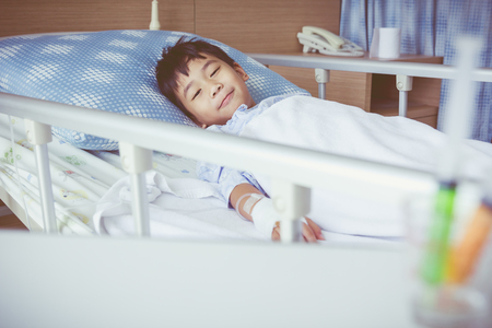 sickbed: Illness asian boy lying on sickbed in hospital with infusion pump intravenous IV drip. Child smile and look at camera. Shallow depth of field child in focus, saline intravenous out of focus. Vintage. Stock Photo