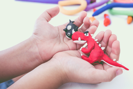 strengthen hand: Close up. Creating red dinosaur and whale clay model