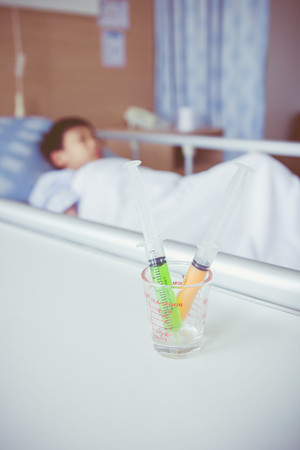 sickbed: Syringes in a glass measuring cup with blurred illness boy lying on sickbed in hospital. Syringe in focus, child out of focus. Health care and medical concept. Vintage style.