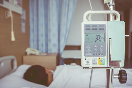 Illness asian boy lying on sickbed in hospital with infusion pump intravenous IV drip. Shallow depth of field, IV machine in focus, child out of focus. Health care and medical concept. Vintage style. Stock Photo