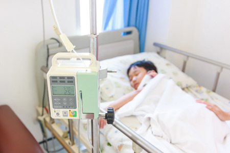 sickbed: Illness asian boy lying on sickbed in hospital with infusion pump intravenous IV drip. Shallow depth of field, IV machine in focus, child out of focus. Health care and medical concept. Vintage style. Stock Photo