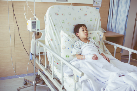 admitted: Illness asian child admitted in the hospital with infusion pump intravenous IV drip. Health care and medical concept. Vintage style.