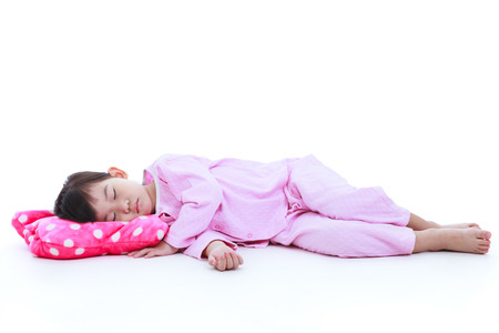 Full body. Healthy children concept. Little asian child sleeping peacefully. Adorable girl in pink pajamas taking a nap. Isolated on white background.