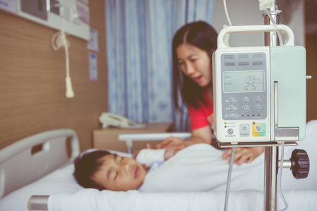 take care: Illness asian child lying on sickbed with infusion pump intravenous IV drip. Mother take care her son. Shallow depth of field, IV machine in focus. Health care and medical concept. Vintage style.