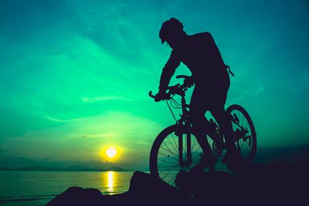 silueta ciclista: Silueta de ciclista montar la bicicleta en un sendero rocoso en la playa, en el fondo colorido del cielo del atardecer. estilo de vida al aire libre activo para el concepto de salud. Foto de archivo