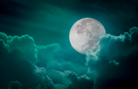 Attractive photo of a nighttime green sky with clouds, bright full moon would make a great background. Nightly sky with large moon. Beautiful nature use as background. Outdoors. Stock Photo