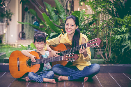 Happy family spending time together. Asian mother with daughter playing classic guitar at home. Pretty girl with thump up and looking at camera. Vintage picture style. Stock Photo