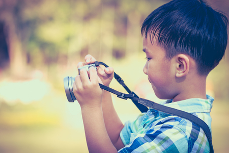 pursuing: Asian boy taking photo by vintage film camera on blurred nature background, on summer in the day time. Child in nature, outdoors. Active lifestyle, curiosity, pursuing a hobby concept. Vintage. Stock Photo