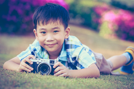 pursuing: Handsome asian boy taking photo by vintage film camera, exploring nature at park, on summer in the day time. Child in nature, outdoors. Active lifestyle, curiosity, pursuing a hobby concept. Vintage.